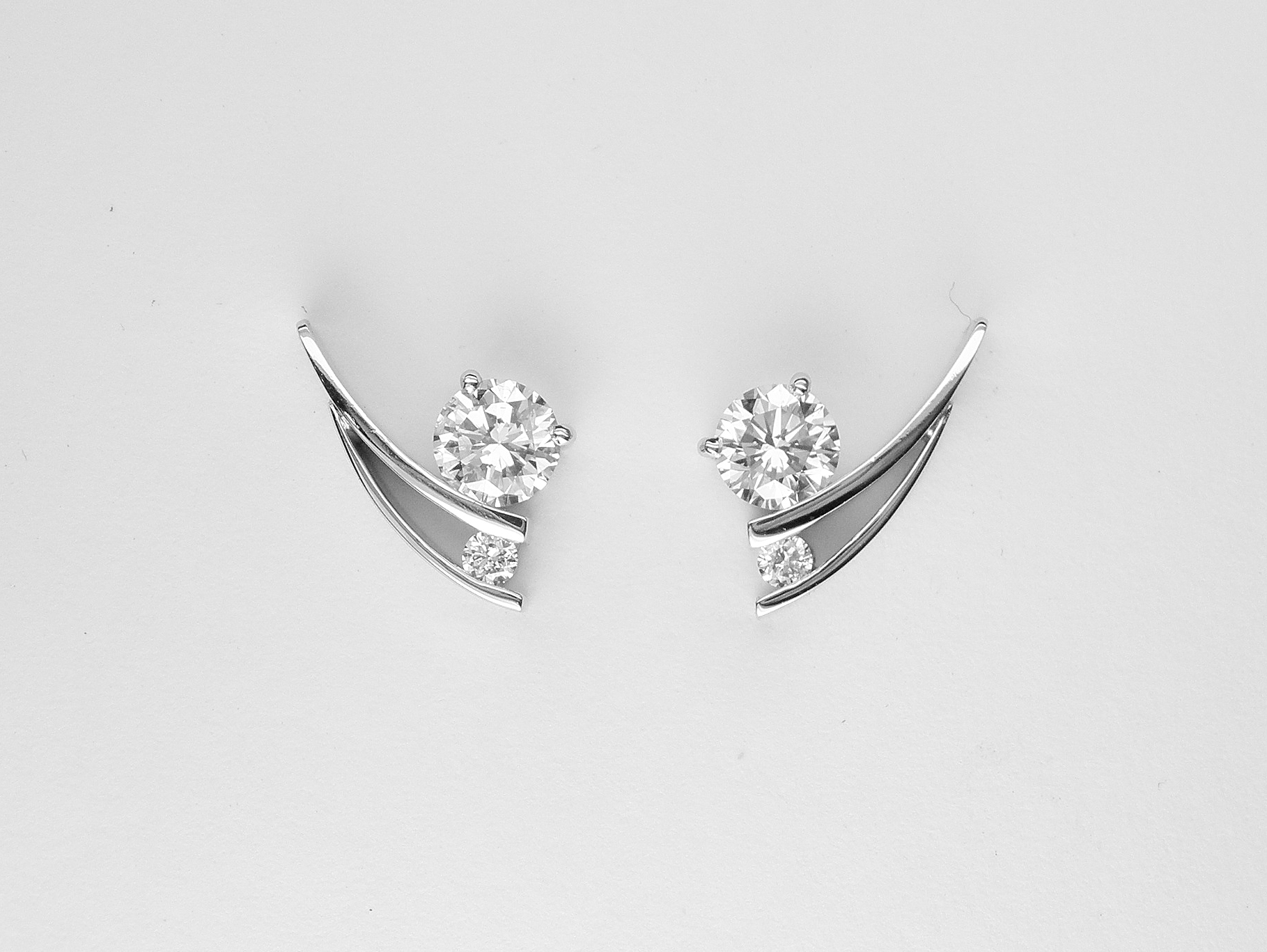 Tick style Platinum & palladium set 2 stone round brilliant cut diamond stud earrings.