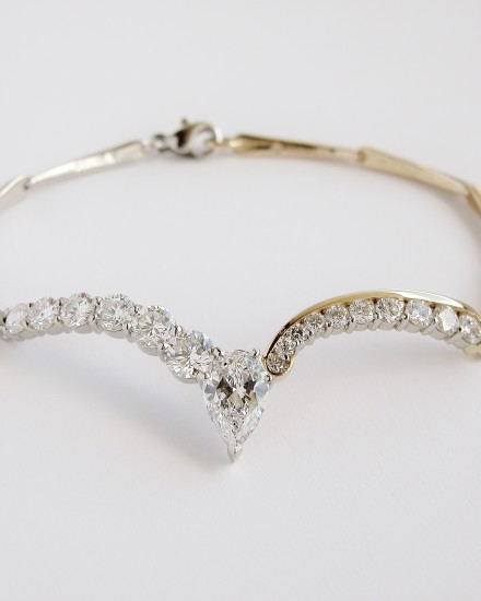 Platinum & 18ct. yellow gold diamond set bracelet with accentual wishbone panel set with a single Pear shaped diamond and 16 round brilliant cut diamonds.