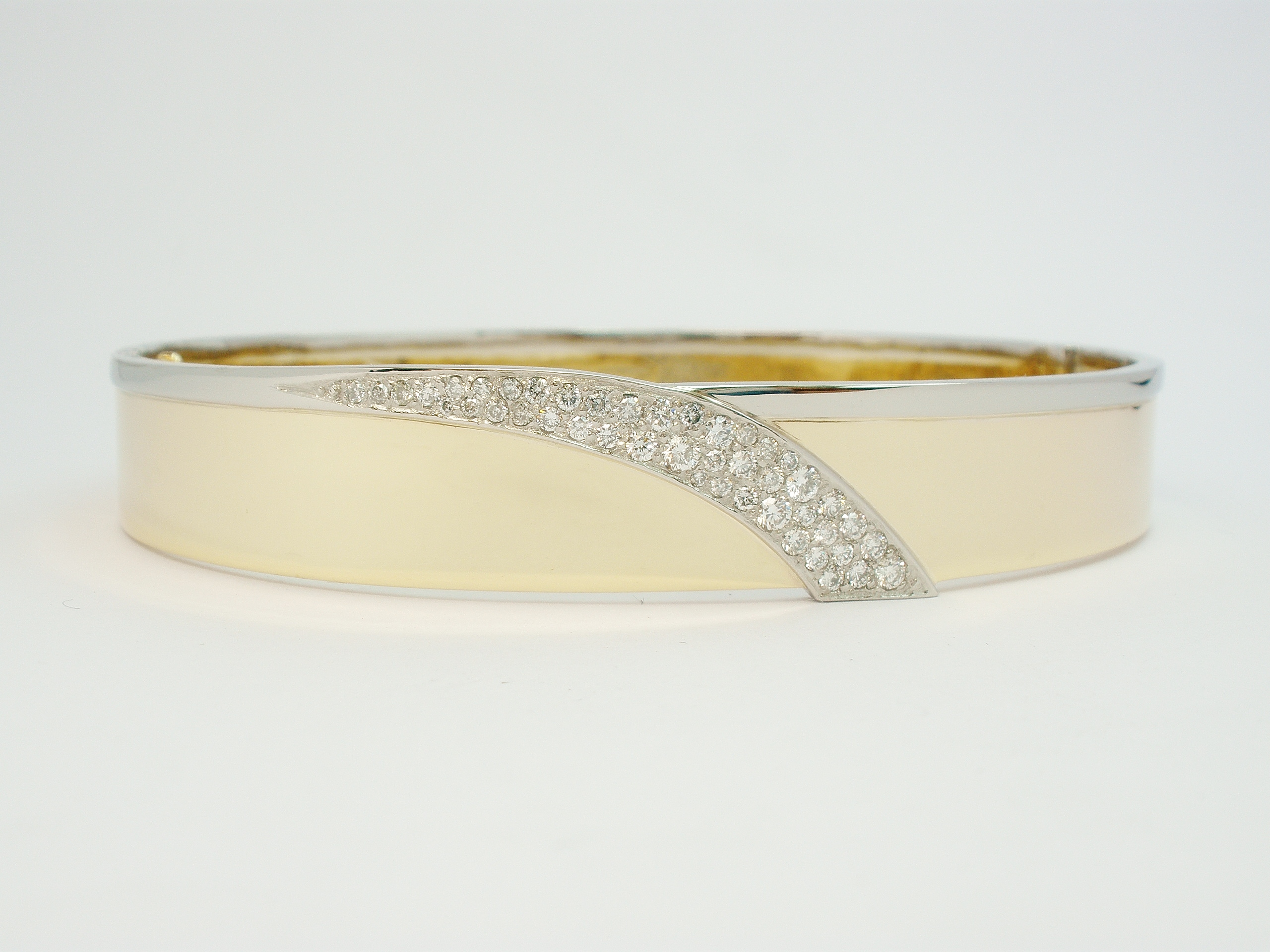 9ct yellow gold and palladium hand crafted hinged bangle with a central cascade shaped palladium panel Pave set with diamonds.