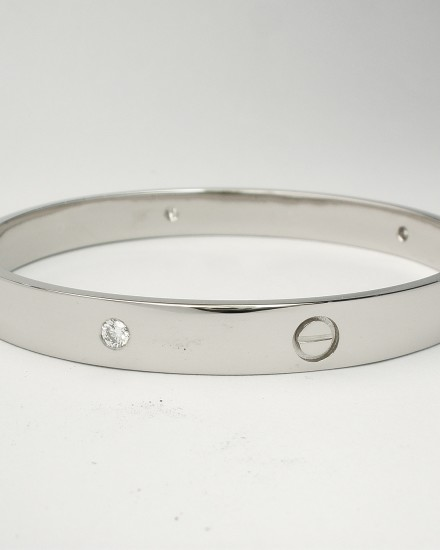 Palladium heavy sectioned bangle flush set with round brilliant cut diamonds and recessed screw heads.