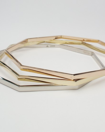 A treo of octagonal bangles one each created from palladium, 9ct. yellow gold & 9ct. red gold (also known as 9ct. rose gold or 9ct. pink gold).