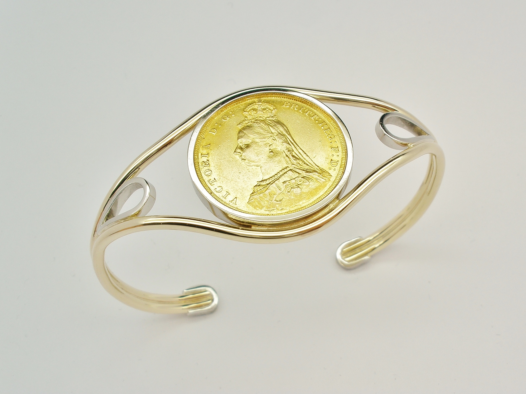 9ct. yellow gold and palladium torque bangle mounted with a single gold full sovereign coin.