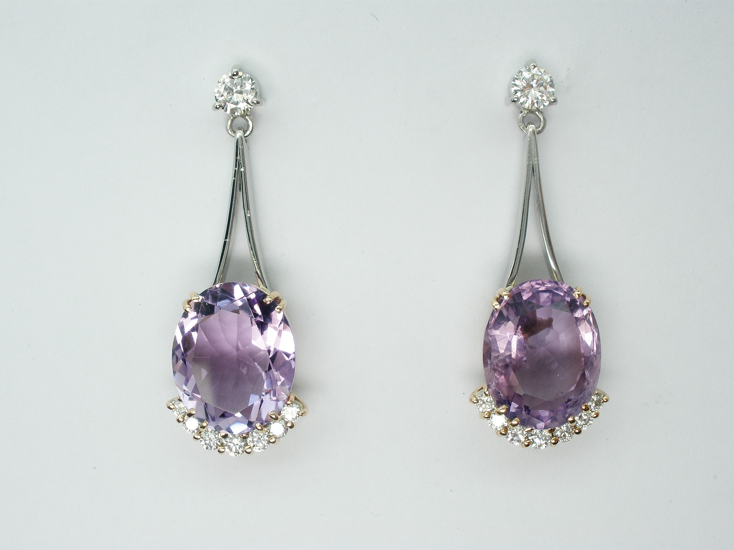 Oval amethyst and round brilliant cut diamond wishbone split wire 'pendulum' style drop earrings.