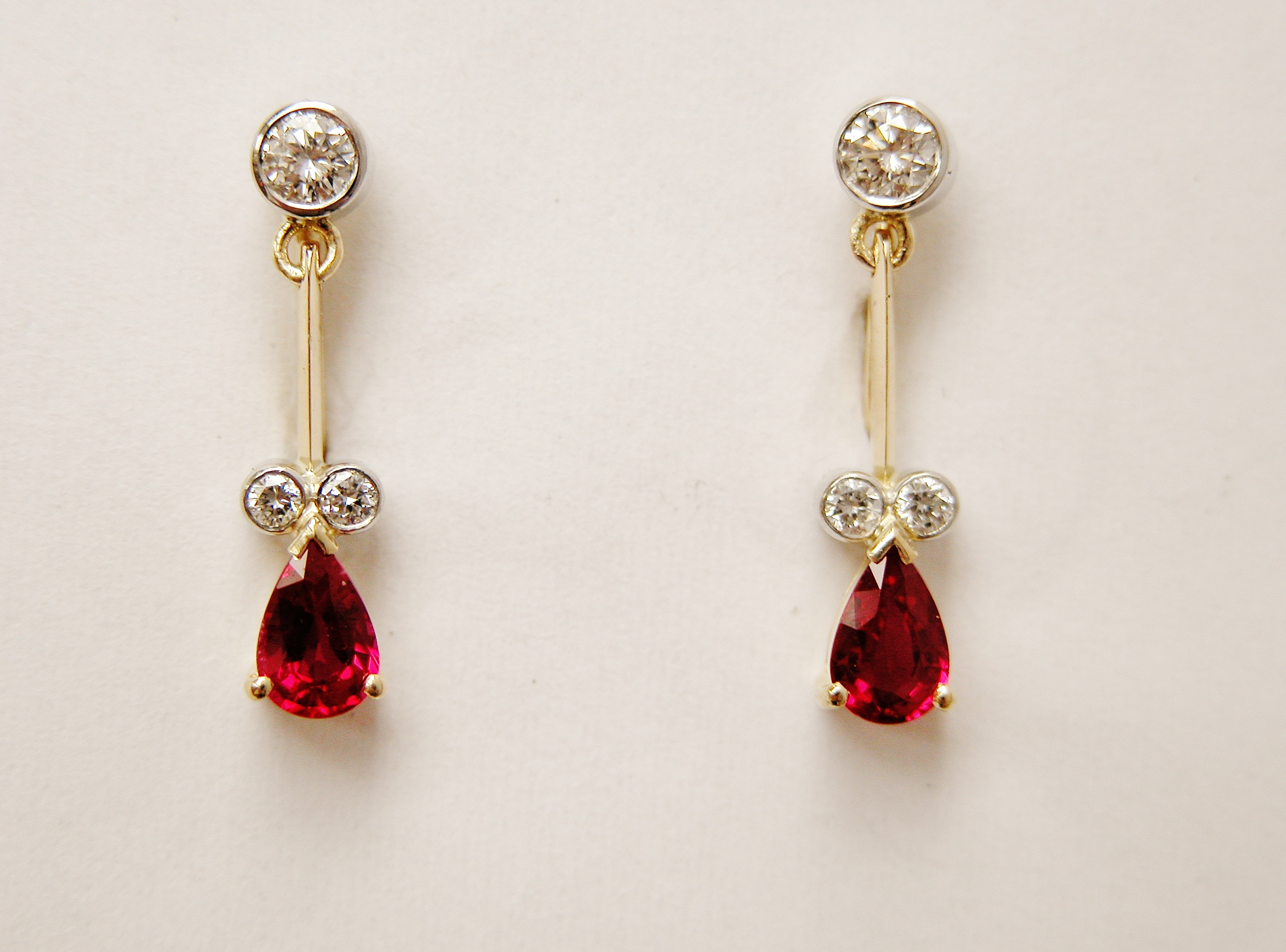 Pear shaped ruby and diamond 18ct. yellow gold pendulum style earrings.