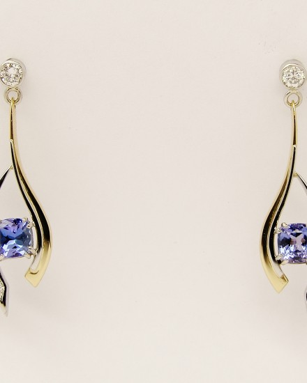 Cushion shaped Tanzanite and round brilliant cut diamond open pendulum earrings set in 18ct yellow gold, palladium & platinum.