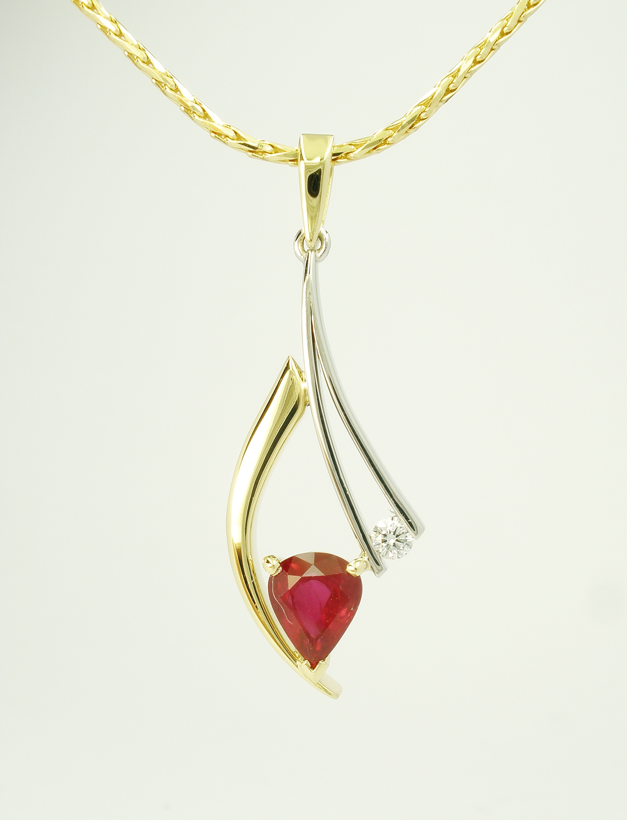 Tear drop shaped ruby and round brilliant cut diamond 18ct. yellow gold horn and fine platinum wire pendant.