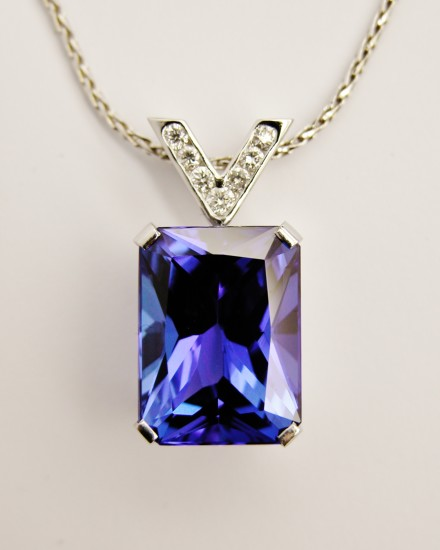 Emerald cut tanzanite pendant set in platinum with a diamond set 'V' shaped platinum shackle.