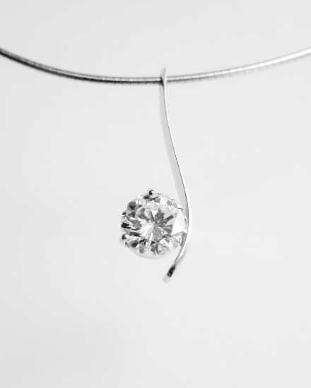 Single stone round brilliant cut diamond 'S' shaped fine platinum wire pendant.