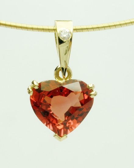 Orange sapphire heart pendant set in 18ct. yellow gold with a diamond set shackle.