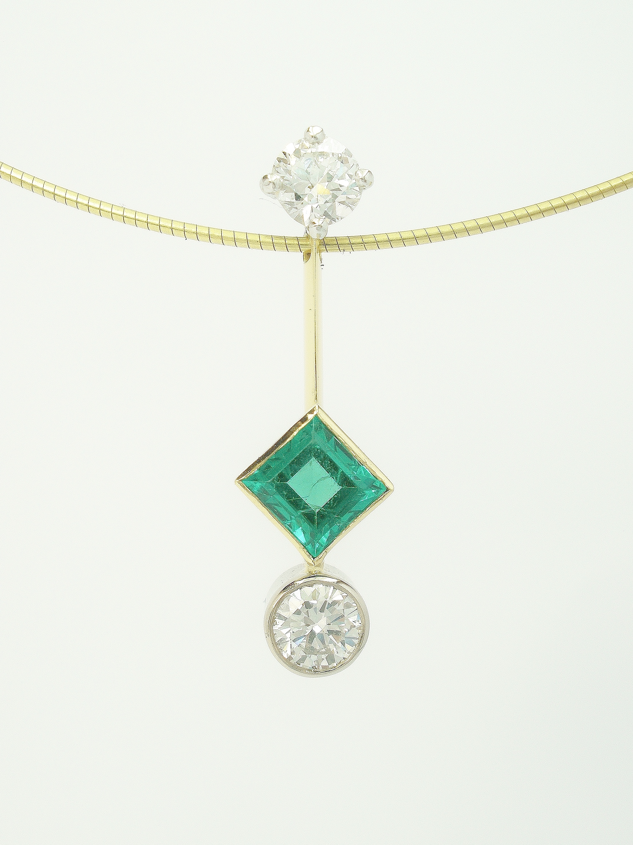 Square cut emerald and round brilliant cut diamond platinum & 18ct. yellow gold 3 stone pendulum style pendant.