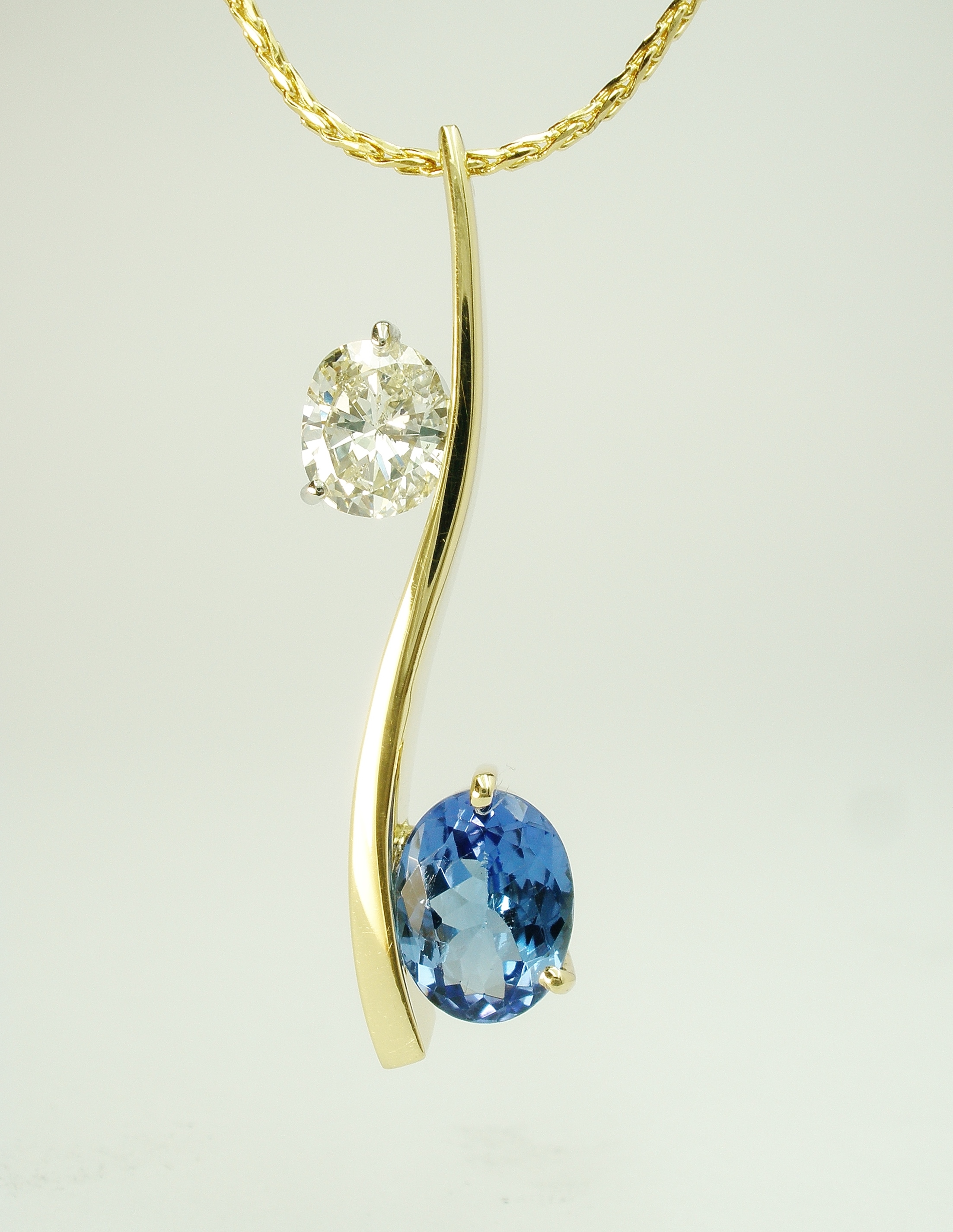 Oval sapphire & oval diamond 2 stone 'S' shaped 18ct. yellow gold pendulum style pendant.