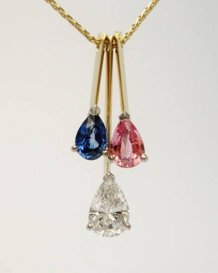 Tear drop shaped diamond,tear drop shaped pink sapphire & tear drop shaped blue sapphire triple 18ct. yellow gold pendulum style pendant.