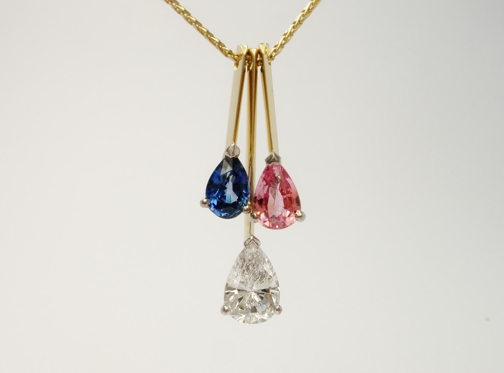 Tear drop shaped diamond,tear drop shaped pink sapphire & tear drop shaped blue sapphire triple 18ct. yellow gold pendulum style pendant.