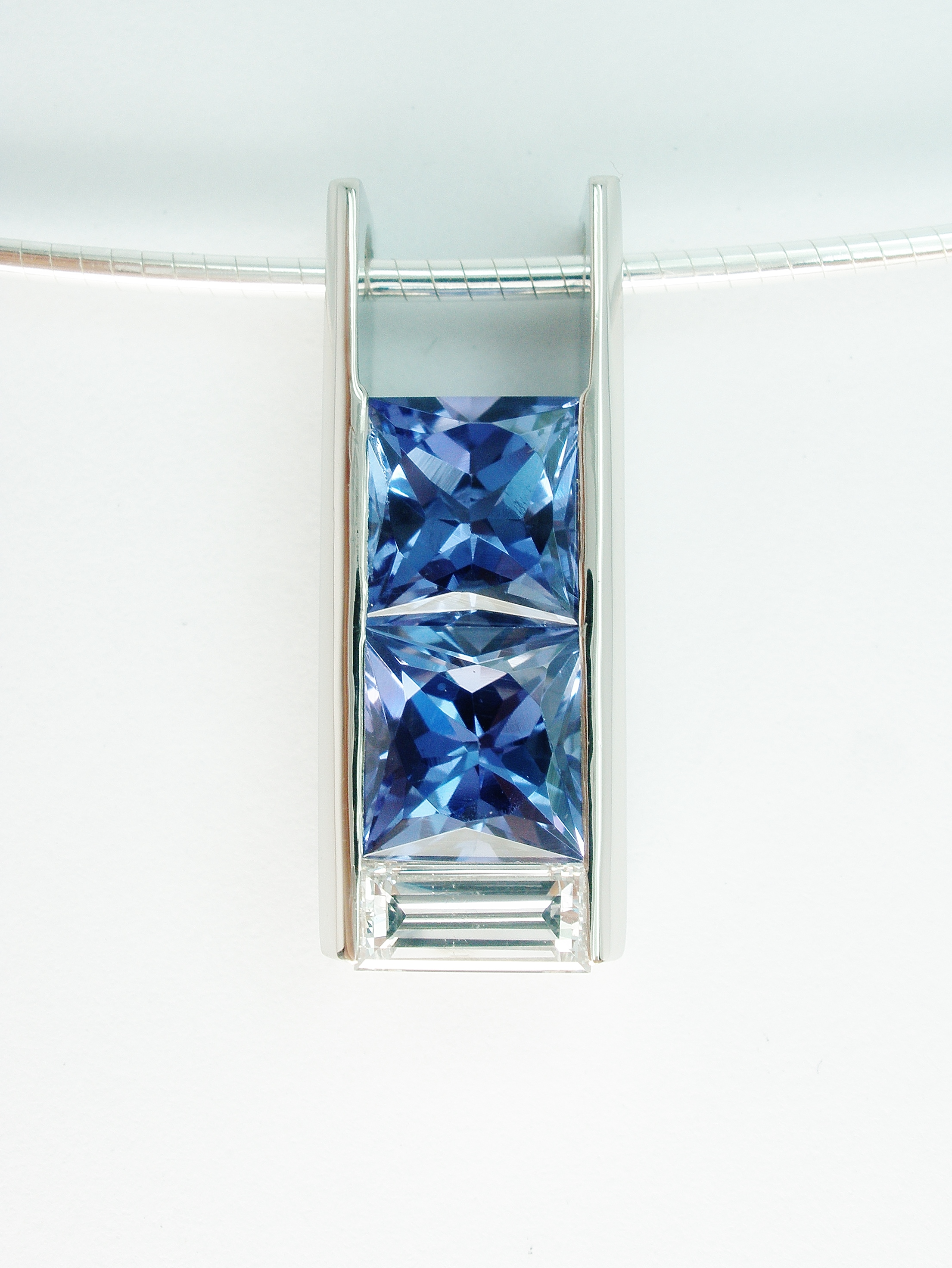 Tanzanite square cut matching pair with diamond baguette set in a box style 18ct. white gold pendant.