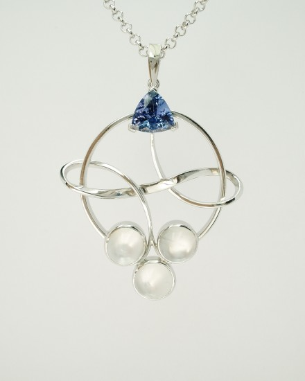 Tanzanite trilliant and moonstone palladium ring and bow pendant.