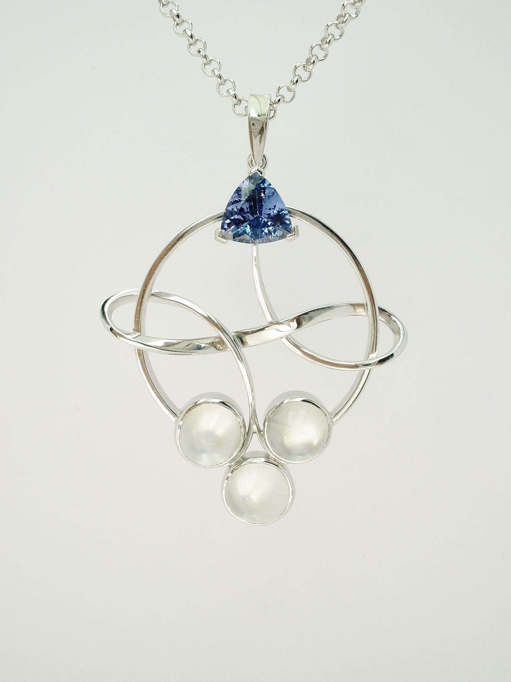 Tanzanite trilliant and moonstone palladium ring and bow pendant.
