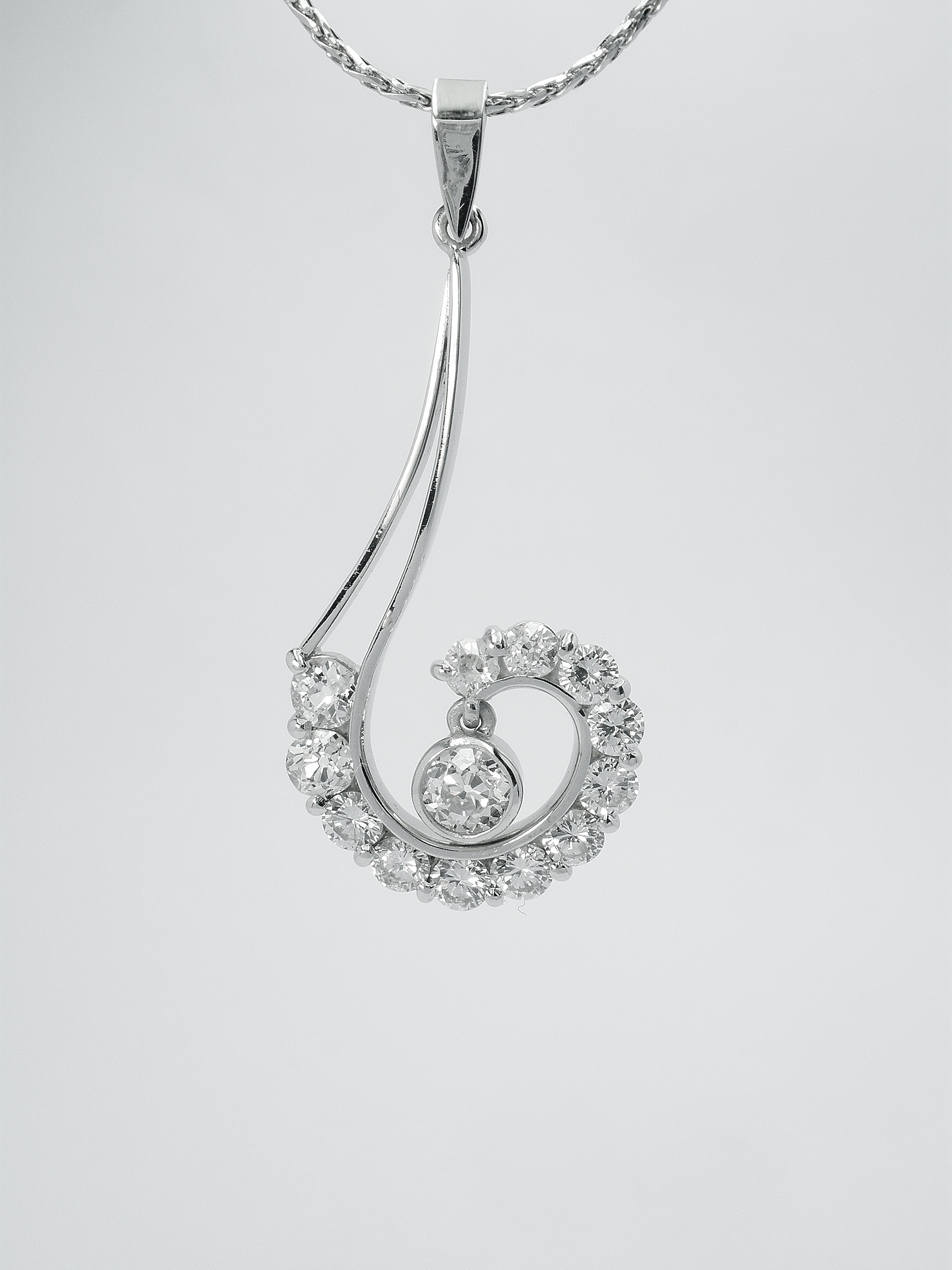 A part channel set platinum & palladium 13 stone diamond pendant in the style of an inverted question mark, with single rub-over set.