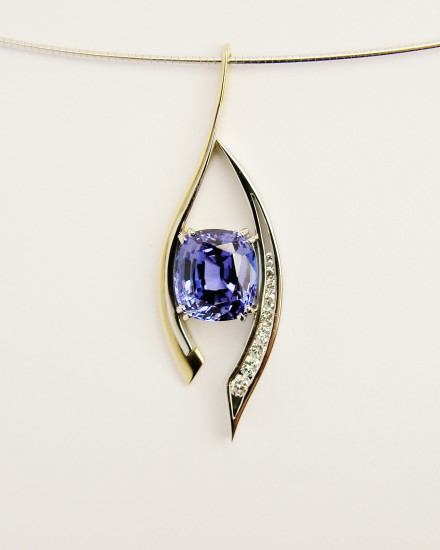 Cushion shaped Tanzanite and round brilliant cutdiamond open pendulum pendant set in 18ct. yellow gold, palladium & platinum.