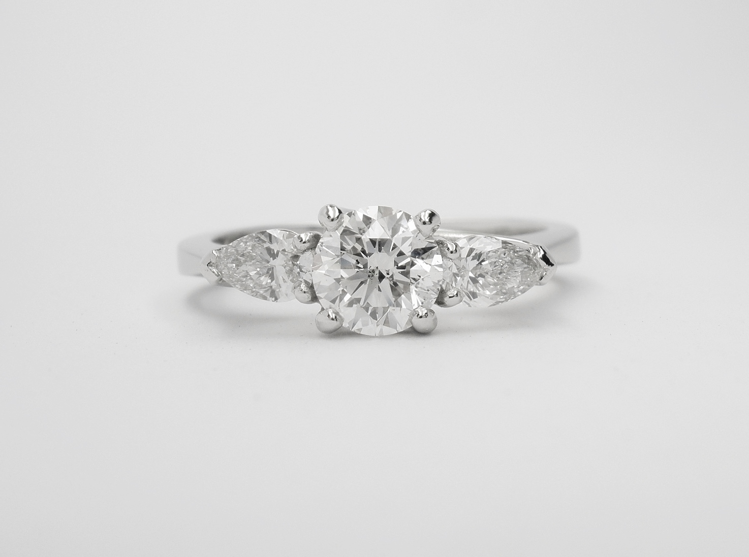 A 3 stone round brilliant cut and pear shaped diamond 'cradle' set ring mounted in platinum.