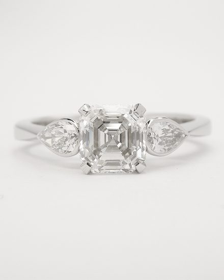 A single 0.82ct. 'E' colour, VS clarity Asscher cut diamond accompanied by a rub-over set pear shaped diamond on each shoulder of the platinum.