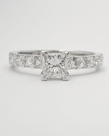A single princess cut diamond ring mounted in platinum with cut-down set round brilliant cut diamonds in the shoulders.