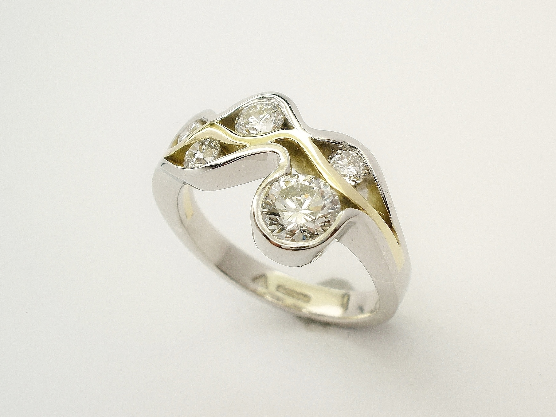 Round brilliant cut diamond 'Wave' ring mounted in Platinum and 18ct. yellow gold.