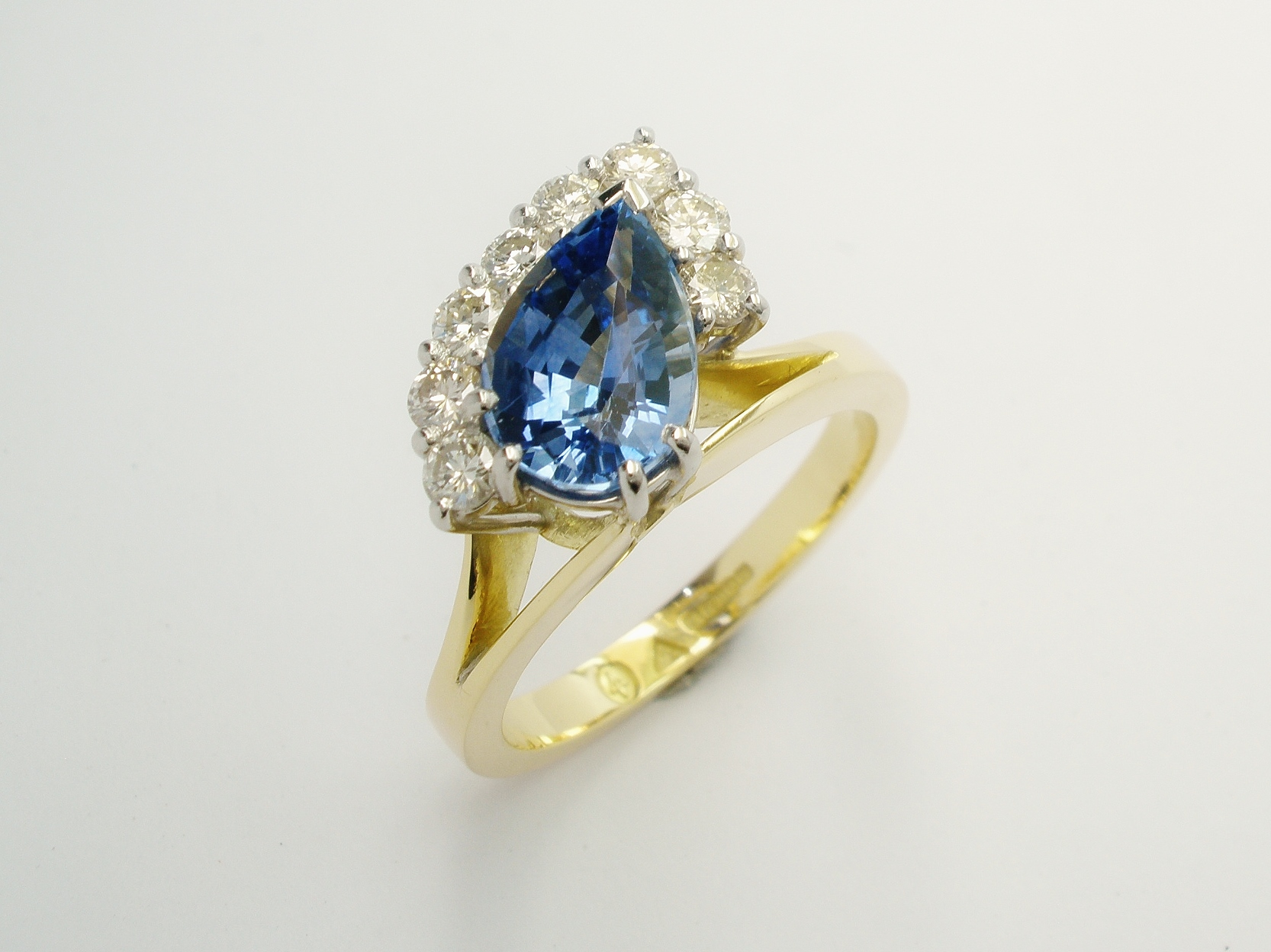 Pear shaped sapphire and round brilliant cut diamond part offset cluster ring mounted in 18ct. yellow gold and platinum.