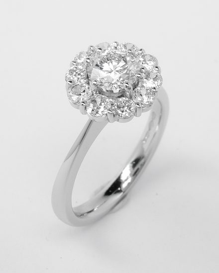 A halo cluster ring comprising 11 round modern brilliant cut diamonds set in platinum. 0.50ct. 'E' colour centre diamond.