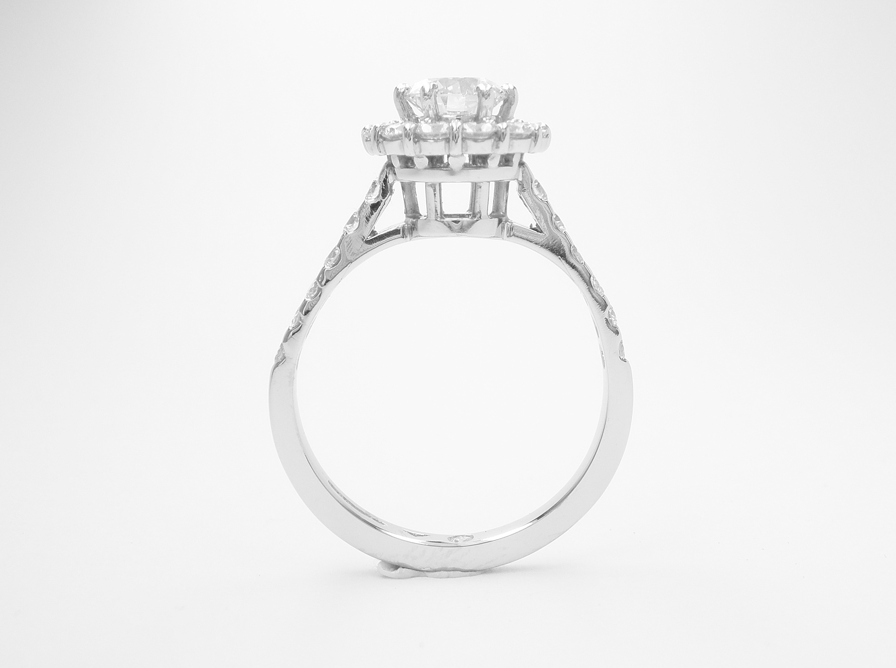 A halo cluster ring comprising of 13 round modern brilliant cut diamonds set in platinum with diamonds cut down set in the shoulders.