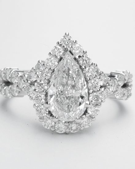 Pear shaped halo cluster ring with centre 0.70ct. 'D'colour pear diamond & criss-cross diamond shoulders set in platinum.