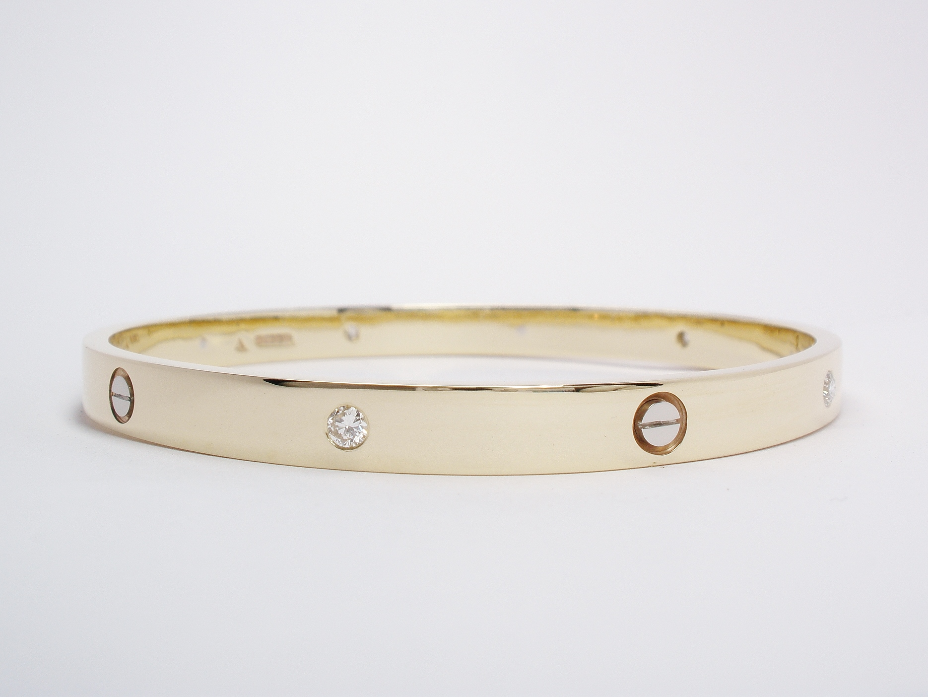9ct yellow gold solid bangle with 5 round brilliant cut diamonds flush set & 5 palladium screw heads inlayed.