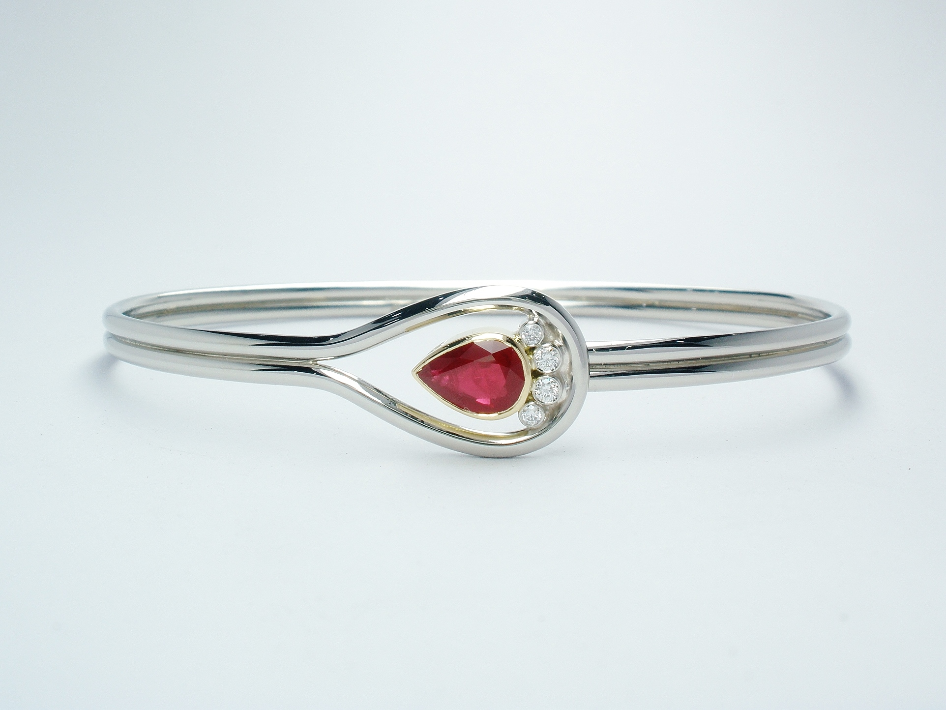 Pear shaped ruby & 4 brilliant cut diamond palladium,18ct. yellow gold & platinum loop style bangle.