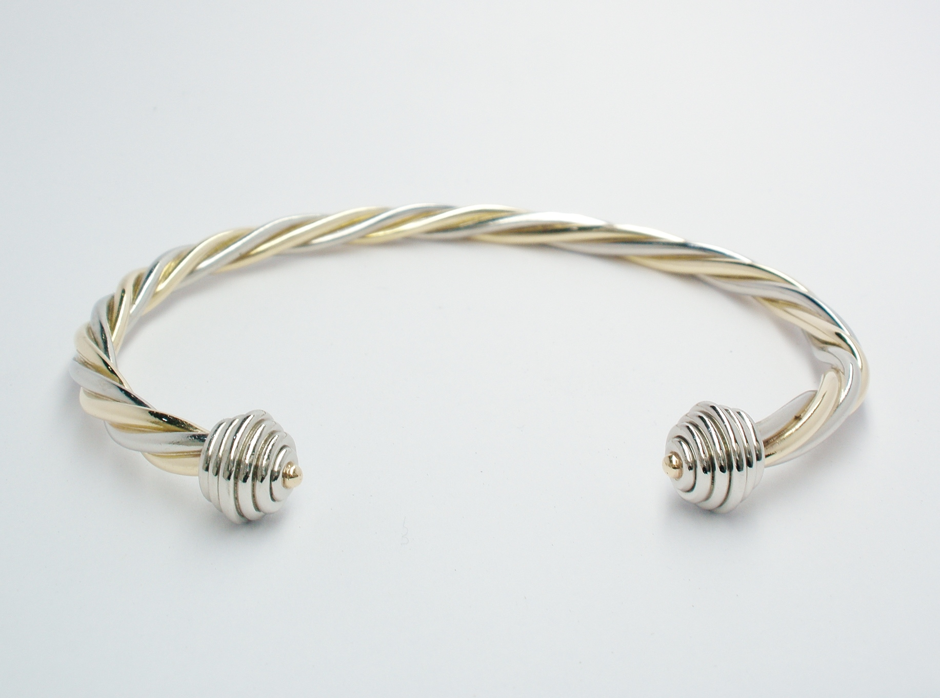 9ct. yellow gold and palladium 2 tone twisted rope style torque bangle with palladium ringed spherical ends.