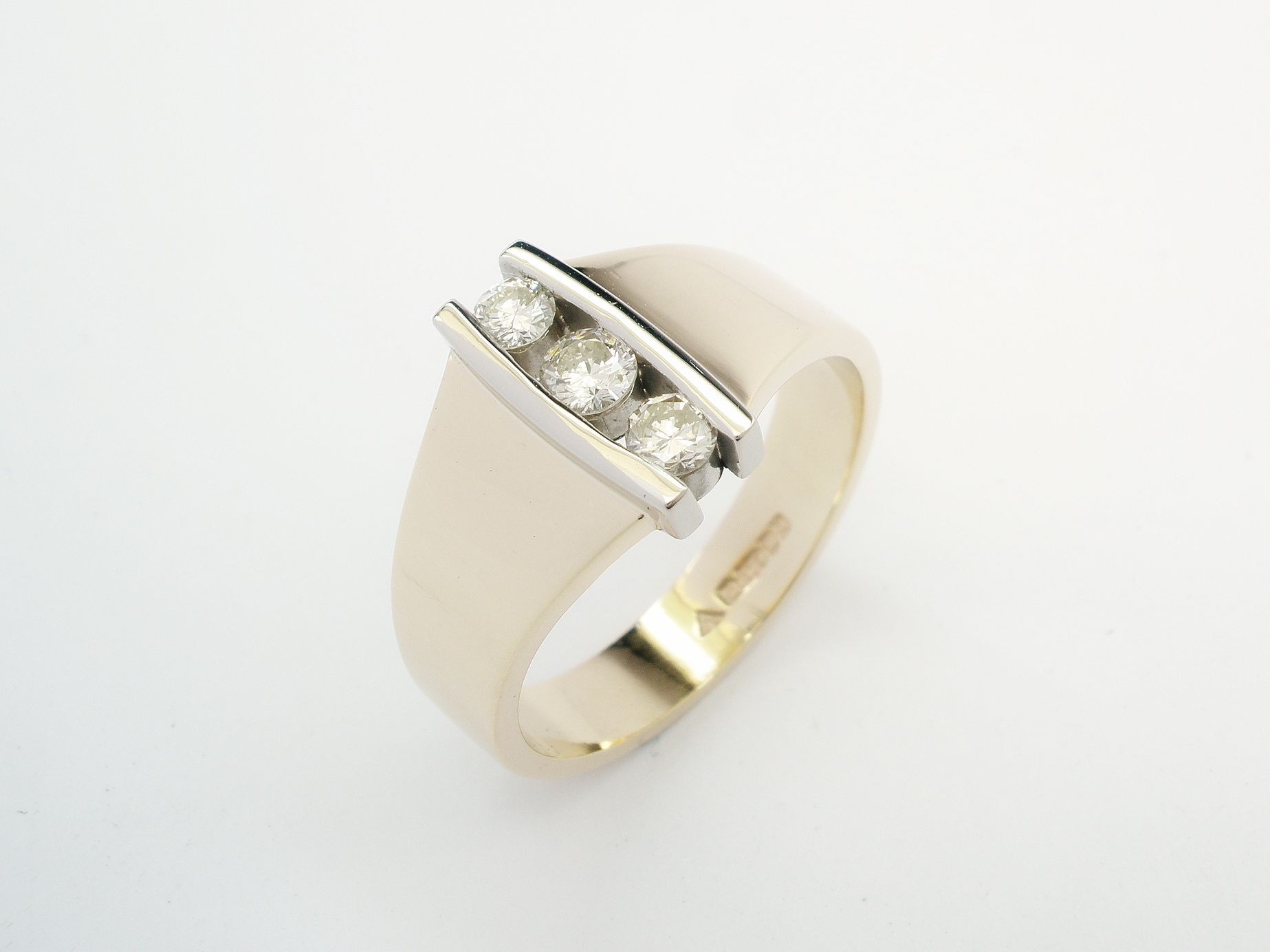 3 stone round brilliant cut diamond vertically channel set 18ct. yellow gold and platinum ring.