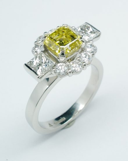 Canary yellow Asscher cut diamond (1.20cts.), white princess cut and round brilliant cut diamond 'Halo' cluster ring mounted in platinum.