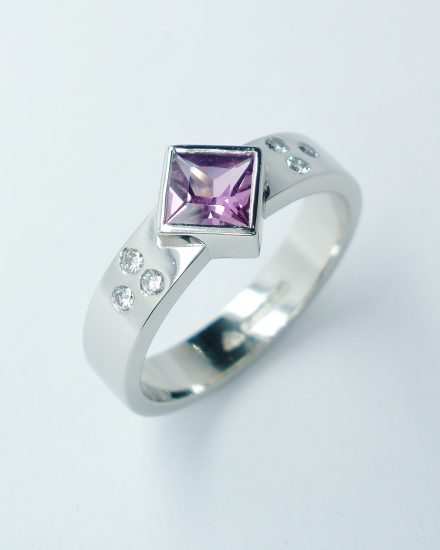 Square princess cut rub-over set purple sapphire and flush set diamond ring mounted in palladium.