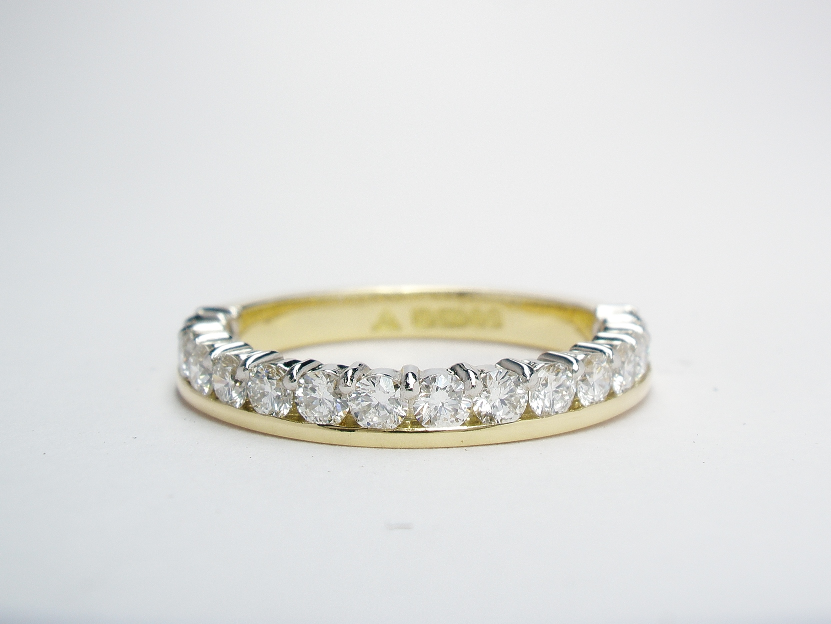 Round brilliant cut diamond eternity ring part channel set to 55% cover, mounted in 18ct. yellow gold and platinum