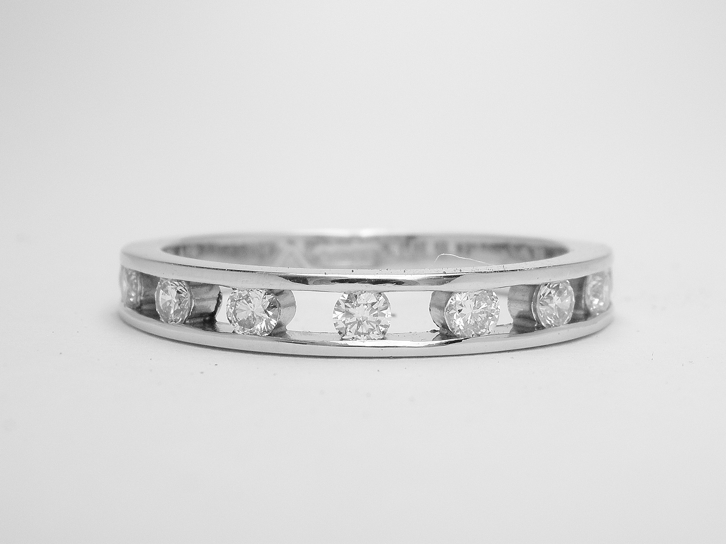 Platinum spaced channel set round brilliant cut diamond eternity ring.
