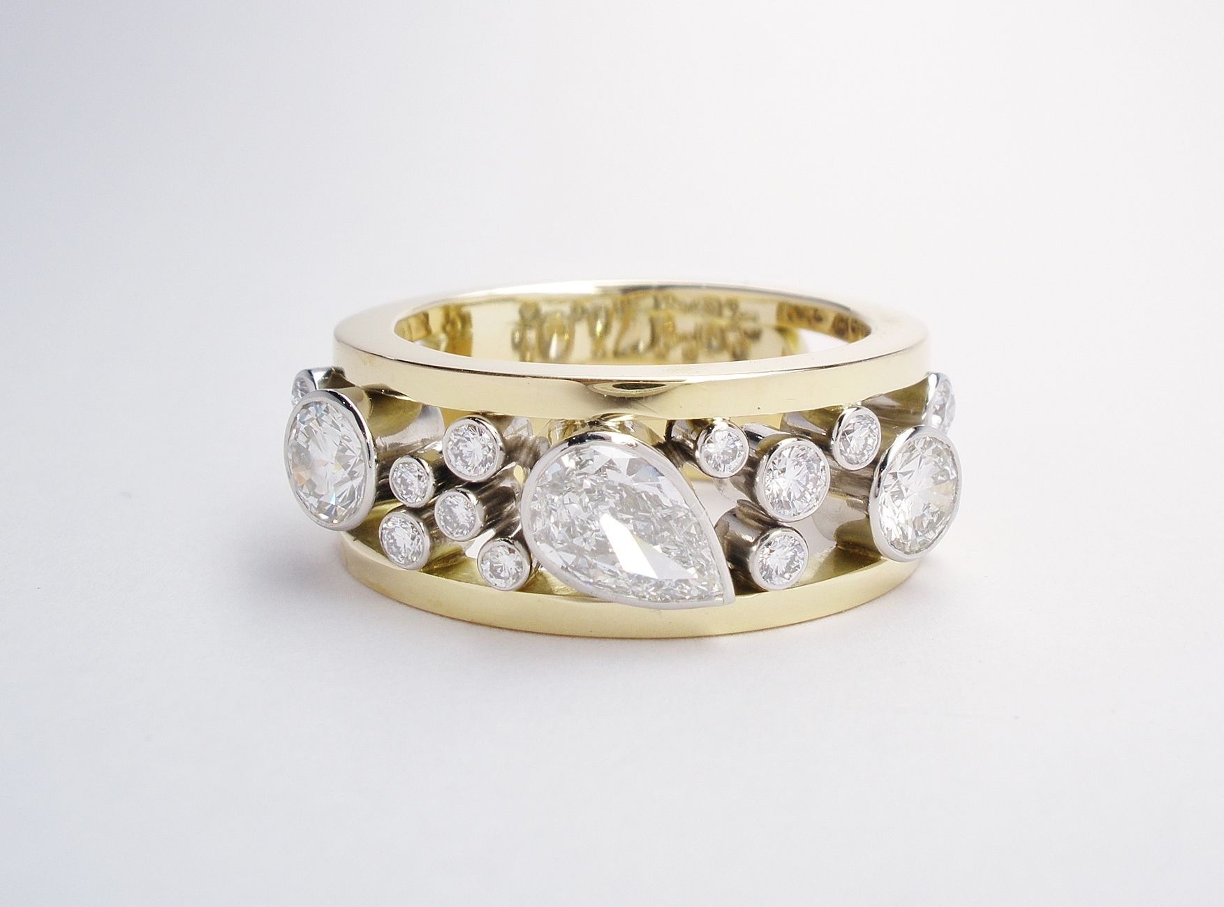 An 18 stone rub-over set pear shaped diamond and round brilliant cut diamond ring mounted in platinum & 18ct. yellow gold.