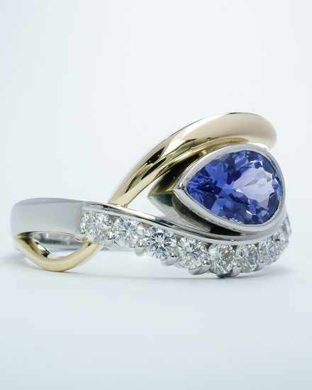 A 12 stone pear shaped tanzanite and round brilliant cut diamond open cross-over ring mounted in platinum & 18ct. yellow gold.