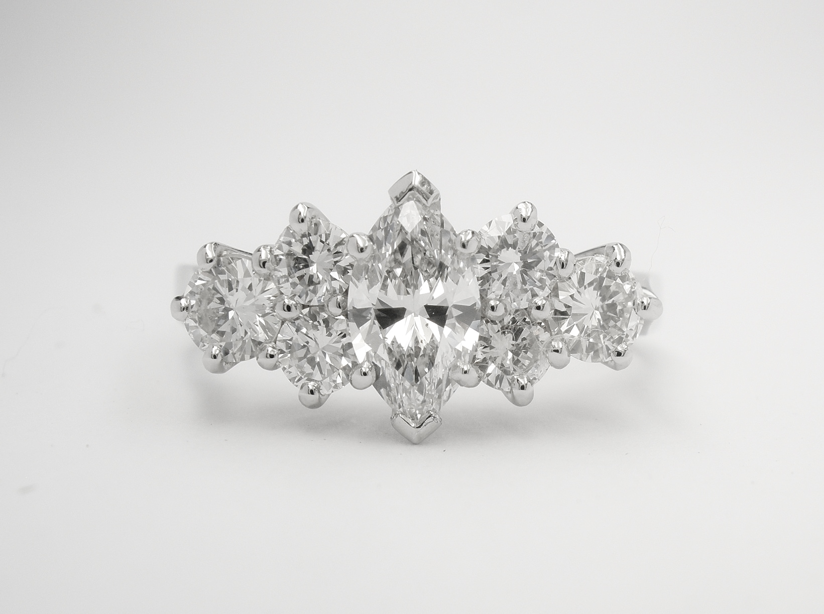 A central marquise diamond flanked on either side with a trefoil of round brilliant cut diamond creating a 7 stone ring mounted in platinum.