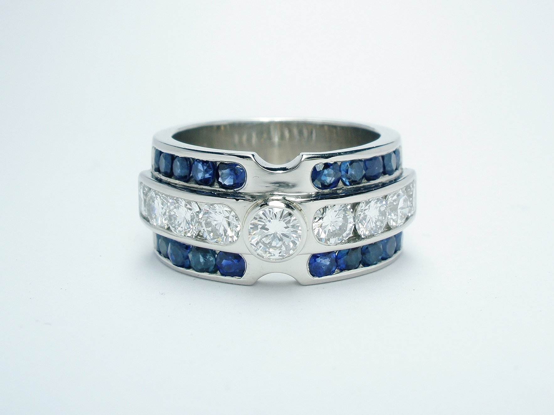 Brilliant cut diamond and round sapphire triple channel set ring mounted in palladium & platinum.