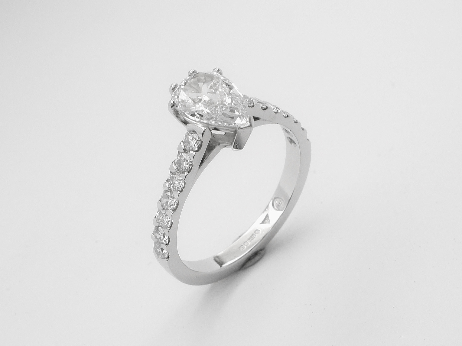 A single pear shaped diamond ring mounted in platinum with round brilliant cut diamonds cut down set in the shoulders.