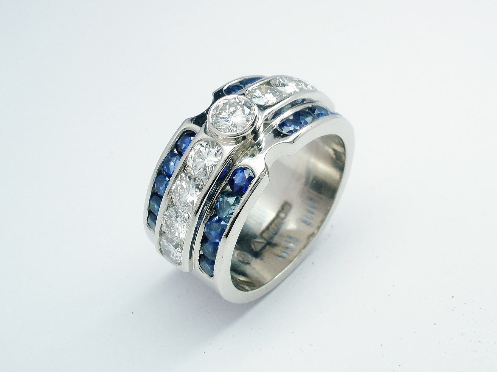 Brilliant cut diamond and round sapphire triple channel set ring mounted in palladium & platinum.