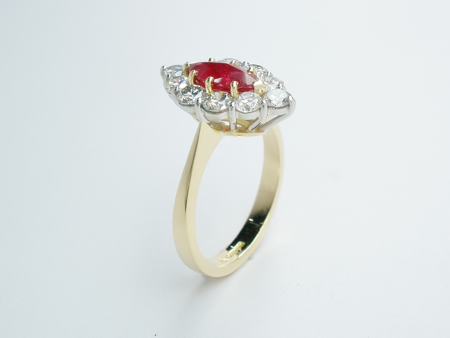 Marquise ruby and round brilliant cut diamond cluster ring mounted in 18ct. yellow gold and platinum.