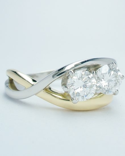 Platinum and 18ct. yellow gold open cross-over 2 stone round brilliant cut diamond ring. Ideal diamond sizes from 0.35cts. to 0.45cts.