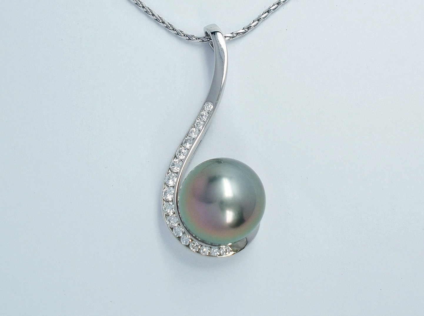 Black Tahitian pearl and round brilliant cut diamond pendant mounted in palladium.
