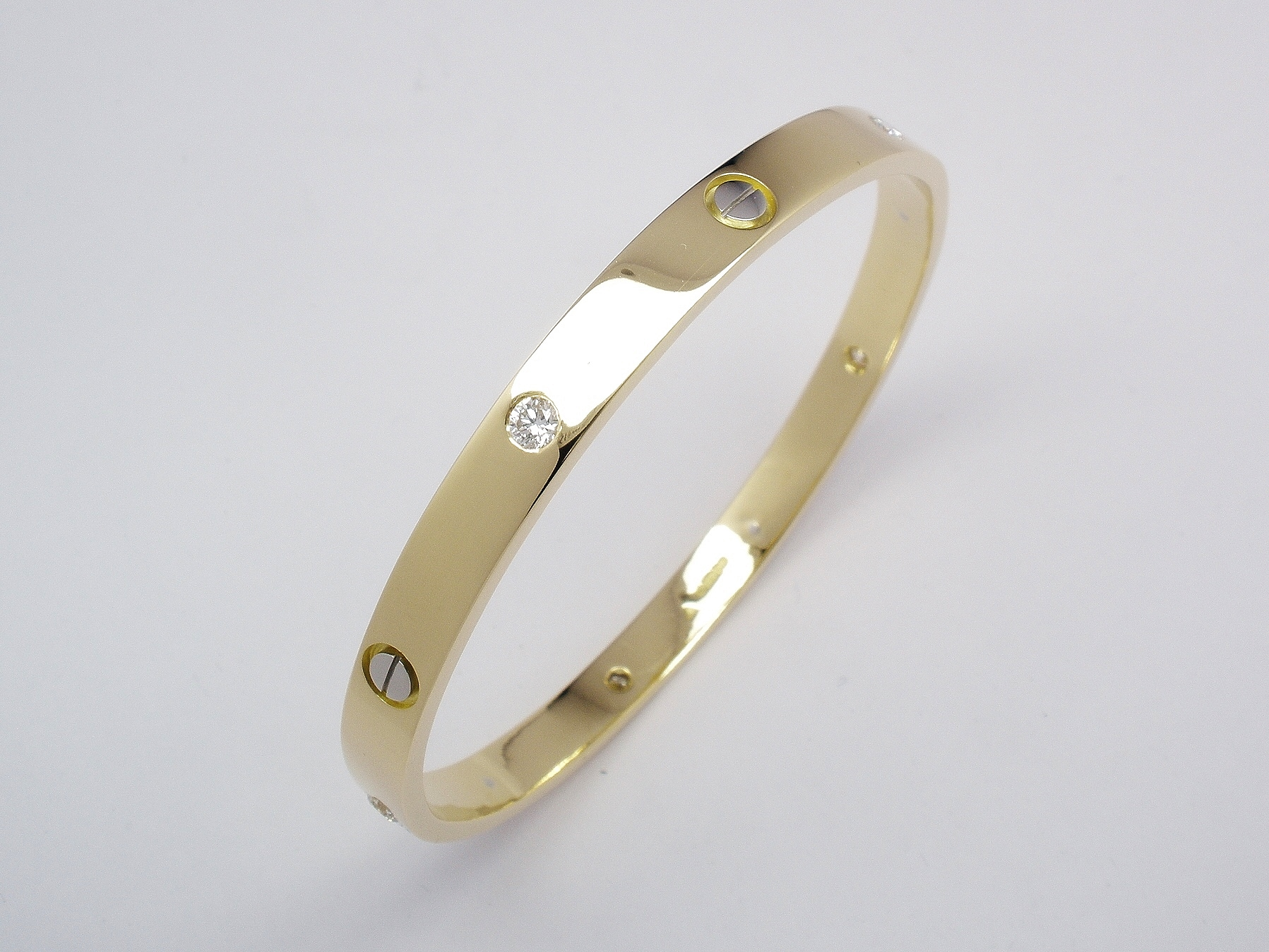 18ct. yellow gold solid bangle with 5 round brilliant cut diamonds flush set and 5 platinum screw heads inlayed.