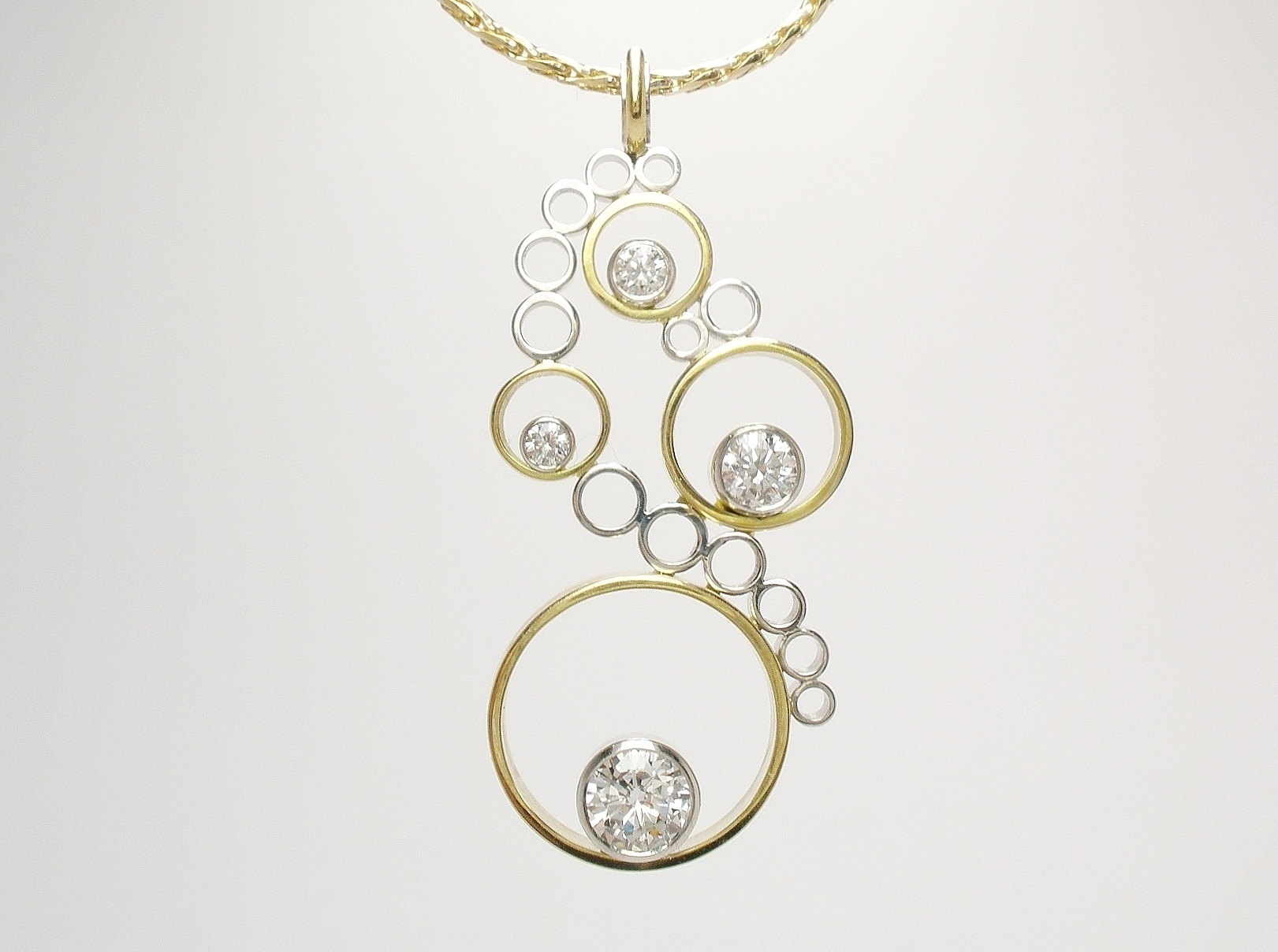 Diamond 4 stone 'Tumble' style pendant mounted in 18ct. yellow gold and platinum.