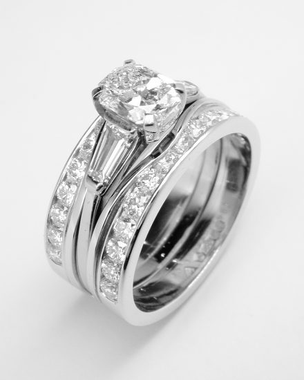 Double 'Embrace' platinum wedding ring channel set with round brilliant diamonds & created to receive the insertion of a phoenix cut and baguette diamond.